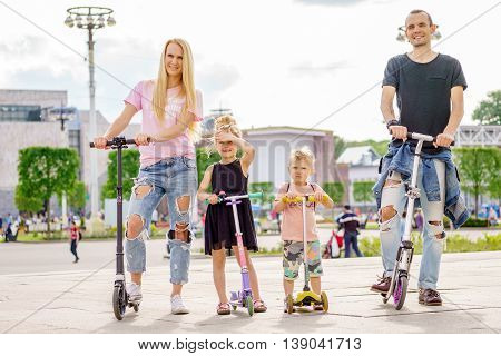 Young modern family with scateboard scooter. family sport