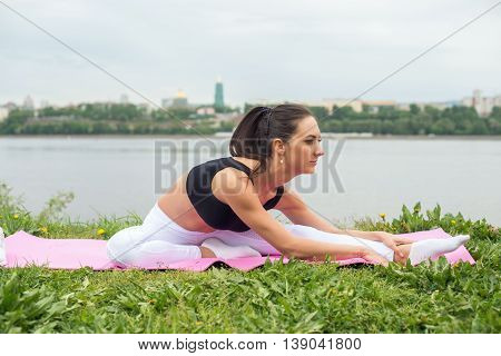 Fit woman stretching legs and back street training, fitness, sport.