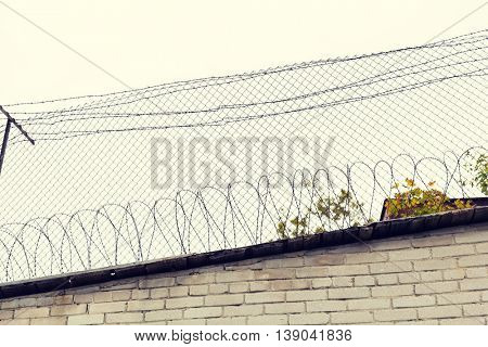 imprisonment, restriction concept - barb wire fence and brick wall over gray sky