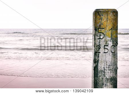 Wooden pillar or pile at the beach. Beach section stake with engraved or carved numbers. Sunset at the beach with selective focus on the foreground and copy space.