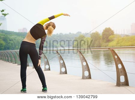 Girl in tracksuit doing stretching. Image with sunflare