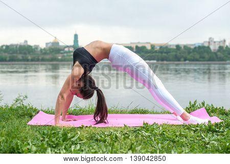Fit woman practicing yoga outdoors Urdhva Dhanurasana Upward bow pose asana exercise