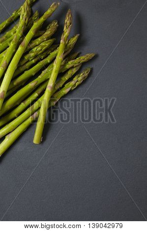 A pile of asparagus spears on a rustic slate background forming a vegetable themed page border