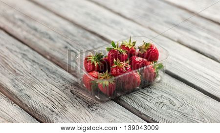 Strawberries in a container. Berries on wooden background. Fresh strawberries for cocktail. Dieting requires vitamins.