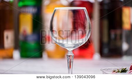 Empty and clean wineglass. Glass on blurred background. Welcome to the bar. Drink anything you want.