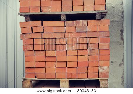 brickwork, construction and building material concept - brown bricks batch on wooden storage tray