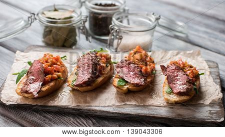 Pieces of baguette with meat. Baked vegetables and herb. Bruschetta with juicy veal. Food for a gourmet.