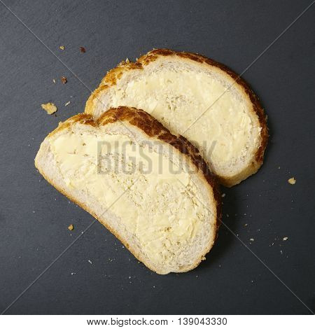 Two slices of buttered crusty bread on a rustic slate chopping board background