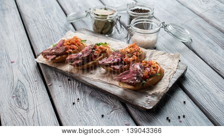 Sandwiches with meat and herb. Gray wooden surface. Meal from italian cuisine. Snack and spices.