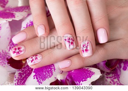 Shot beautiful manicure with flowers on female fingers. Nails design. Close-up. Picture taken in the studio on a white background.