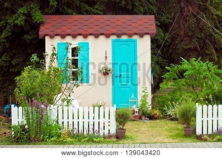 Facade of small house with aqua window and door, pot flowers on the wall and garden view
