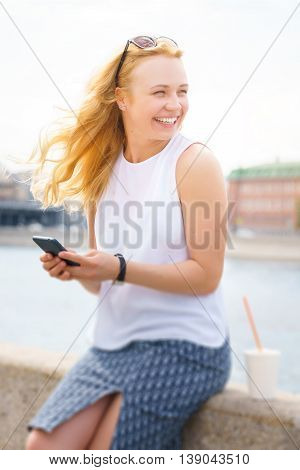 Portrait of beautiful blonde with phone on promenade. Young woman smiling and looking away. Image with tilt-shift effect