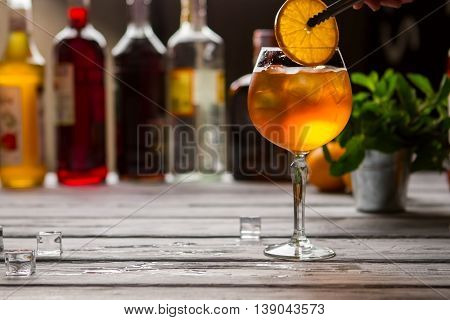 Wineglass with orange drink. Tongs hold slice of orange. Aperol spritz served at bar. Soda water and sparkling wine.