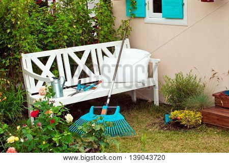 White bench in the yard, gardening instruments