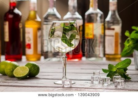 Cocktail with ice in glass. Mint leaves and limes. Sweet syrup for Hugo drink. Beverage is almost ready.