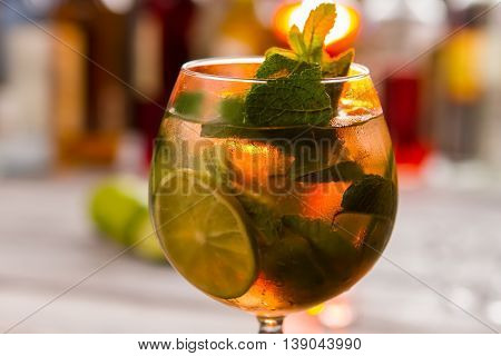 Beverage with mint leaves. Cocktail in wineglass. Sweet syrup and mineral water. Fresh and cool hugo drink.
