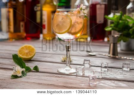 Beverage with slice of lemon. Wineglass decorated with flower. Juicy citrus fruit and ice. Refreshing taste of tom collins.