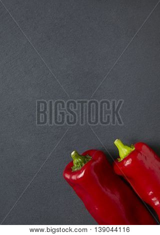 Sweet red peppers on a rustic slate background forming a cooking themed page border