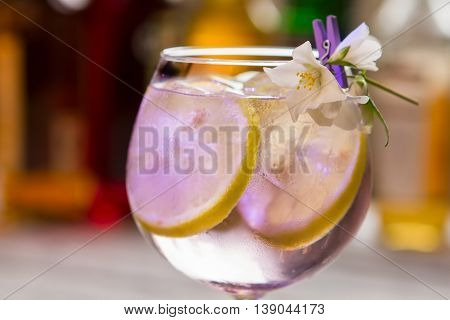 Lemon slices in transparent drink. Cocktail in decoreted wineglass. Expensive beverage made at bar. How to make tom collins.