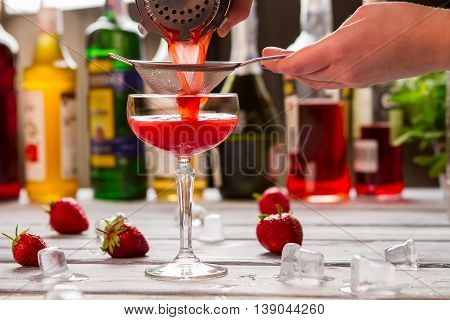 Red drink pours through sieve. Ice cubes near coupe glass. Bartender makes clover club. Juice of fresh berry.