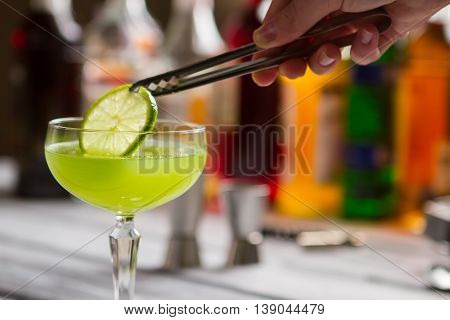 Green drink in coupe glass. Tongs hold slice of lime. Delicious beverage with sour juice. Fresh taste of kiwi daiquiri.