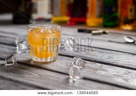 Orange drink in a glass. Glass on gray wooden surface. Cold cocktail with juice. Don't let yourself boil.