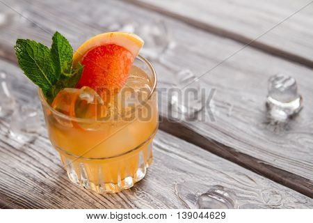 Orange drink with ice cubes. Grapefruit slice and mint. Bartender made an exotic beverage. Cobas cocktail with cinnamon.