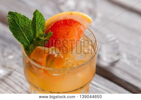 Beverage of orange color. Piece of grapefruit and ice. Fresh juice and cinnamon. Freshen up your summer.