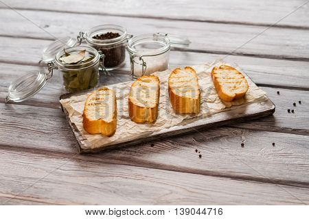 Slices of grilled baguette. Jar with bay leaves. Best bread for tasty sandwiches. Set of essential spices.