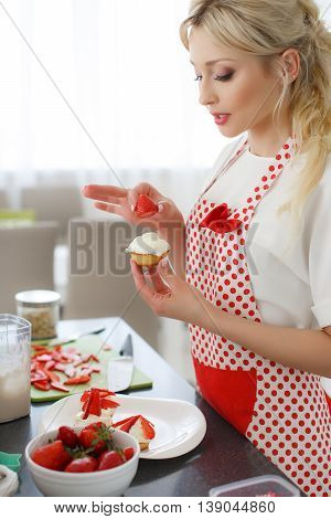Young beautiful woman,blonde hair,light makeup and pink lipstick,wearing earrings,wearing a white t-shirt and white red polka dot pinafore,engaged in the bright kitchen cooking cupcakes