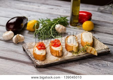 Baguette slices with vegetables. Toasts and piece of lemon. Crispy bruschetta with tomatoes. Example of italian food.