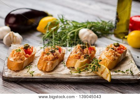 Small toasts with fish meat. Capers and slice of lemon. Bruschetta with salmon and tomatoes. Extremely delicious meal.