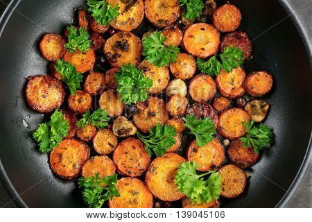 Fried sliced carrot with parsley on frying pan