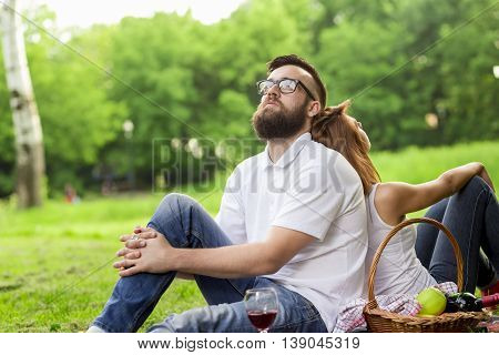Couple sitting on a picnic blanket both pensive enjoying the peace and nature