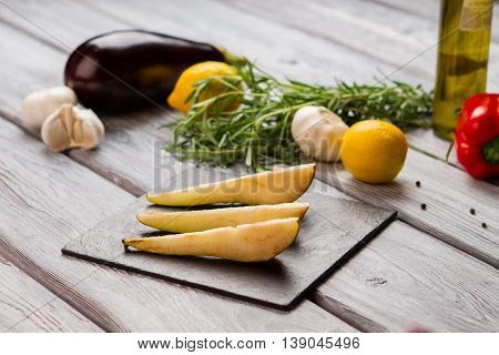 Slices of pear. Garlic and green herb. Fruit for special dish. Organic food ingredients on table.