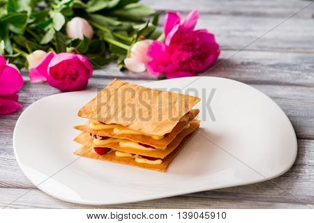 Puff with custard on plate. Bright pink flowers. Raspberry millefeuille served at restaurant. Sweet dish for a gourmet.