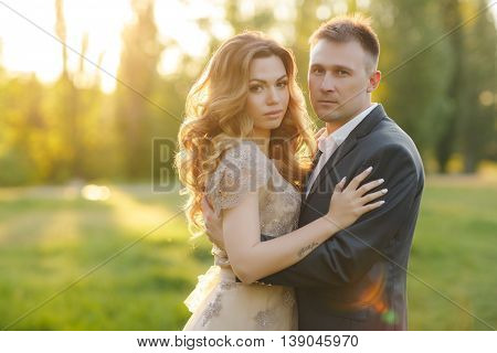 A young couple in love,bride and groom,blonde woman and man in wedding attire,standing arm in arm on a green summer meadow at sunset,romantic moments of the wedding