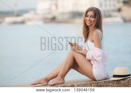 Young beautiful woman with a beautiful smile,long blonde straight hair,wearing a light pink and white shirt stripe and a white t-shirt,sitting on the embankment near the blue ocean,looking through the messages on his mobile phone,lying next to a hat