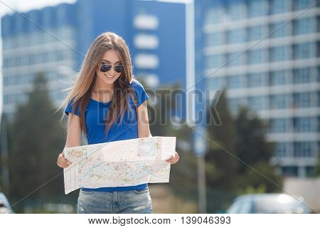 Pretty brunette woman with long straight hair and gray eyes,long eyelashes and light make-up,dressed in a blouse of blue color,wears dark sun glasses,stands amid the blue-and-white tall building in the hands holding a detailed map of the city