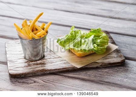 Bucket of fries and bread. Green lettuce leaf. Recipes for homemade food. How to make a sandwich.