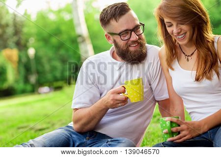 Young couple in love sitting on a picnic plaid in a park drinking coffee and enjoying their day out in nature