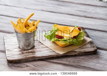 Small bucket of fries. Bread with lettuce and cheese. Fresh food products. Recipe with simple ingredients.