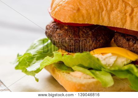 Burger with lettuce leaves. Cream cheese and grilled meat. Old recipe of cheeseburger. Huge amount of calories.