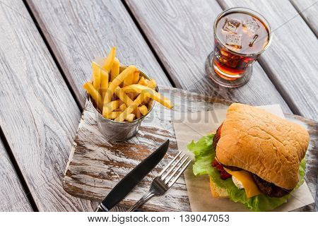 French fries and burger. Cutlery and glass with cola. Appetizing meal in cafe. It's time for dinner.