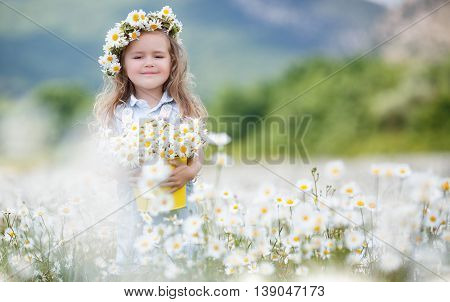 Beautiful little girl with long curly blond hair,cute smile,in a light blue denim overalls,a white wreath of fresh flowers in the hands holding a yellow bucket with a field of daisies,picking flowers on a mountain meadow in summer