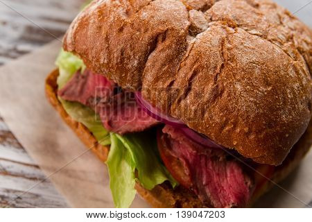 Sandwich with lettuce. Brown bread and purple onion. Rustic recipe of sandwich. Veal and fresh juicy onion.