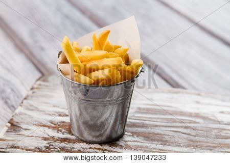 Yellow fries in small bucket. Gray wooden surface. Yummy fast food dish. Carbohydrates and fats.