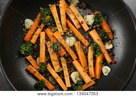 Healthy food and ingredients with sliced carrots, parsley and spices in a pan