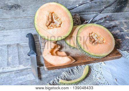 Slices of ripe melon on a chopping board with a knife and napkins