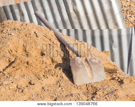 The old iron shovel with a wooden handle lies on a pile of yellow sand interspersed with gravel on a construction site against the backdrop of gofrolist